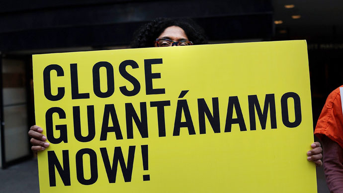 "A woman holds up a sign while participating in a nationwide ""Day of Action to Close Guantanamo & End Indefinite Detention"" on April 11, 2013.(AFP Photo / Spencer Platt)"
