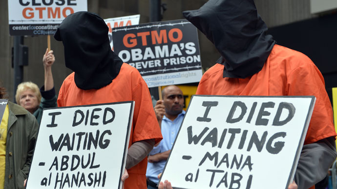 People dress in orange jumpsuits and black hoods as activists demand the closing of the US military's detention facility in Guantanamo during a protest, part of the Nationwide for Guantanamo Day of Action, April 11, 2013.(AFP Photo / Stan Honda)