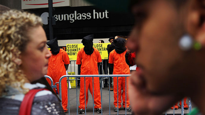 "Pedestrians in Times Square watch as protesters, dressed in orange prison jumpsuits, participate in a nationwide ""Day of Action to Close Guantanamo & End Indefinite Detention"" on April 11, 2013.(AFP Photo / Spencer Platt)"