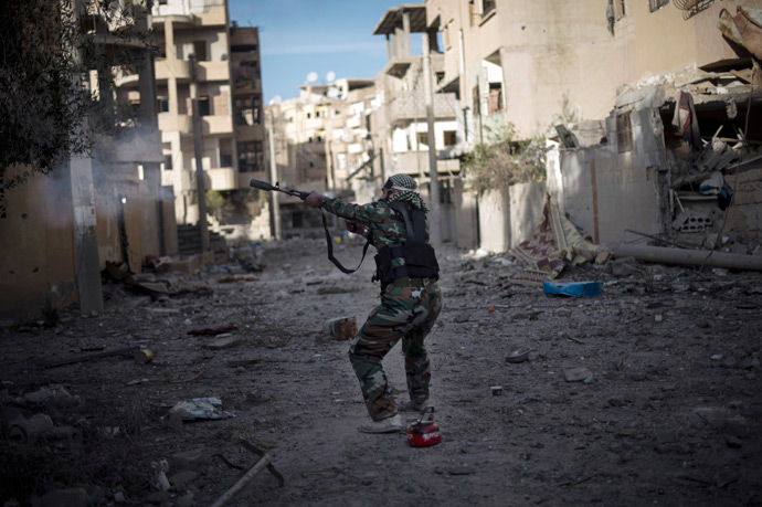 Syrian rebel from the Shuhaa Arfie brigade, uses his modified rifle to fire a home made pipe bomb towards government positions (AFP Photo / Zac Baillie)