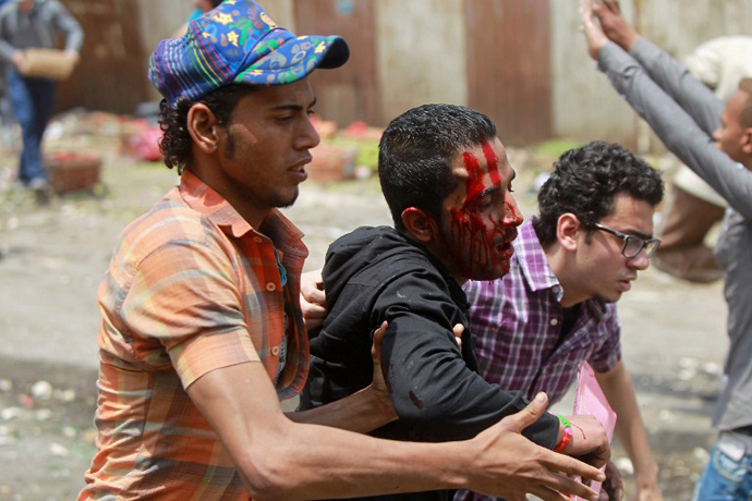 Egyptian anti-military protesters help a wounded demonstrator during clashes in the Abbassiya district of Cairo on May 2, 2012. (AFP Photo / Khaled Desouki)