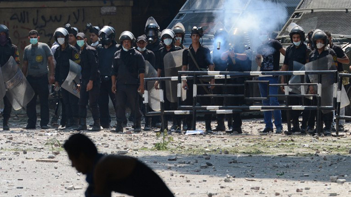 An Egyptian riot police officer fires tear gas towards protesters. (AFP Photo / Khaled Desouki)