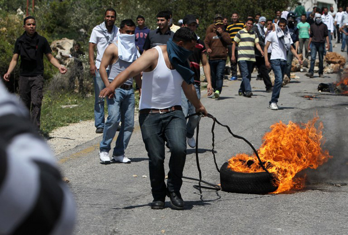 A Palestinian pulls a tyre in fire during clashes with Israeli forces following a protest against the expropriation of Palestinian land by Israel in the West Bank village of Silwad, east of Ramallah, on April 12, 2013. (AFP Photo / Abbas Momani)