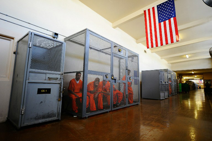 Inmates at Chino State Prison sit inside a metal cage in the hallway in Chino, California. (AFP Photo / Kevork Djansezian)