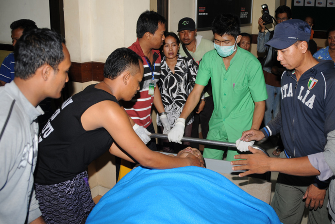 An injured passenger (C) from the Lion Air plane that missed the runway at Bali's international airport is attended to at hospital as people arrive for treatment in Kedongan near Denpasar on Bali island on April 13, 2013 (AFP Photo / Sonny Tumbilaka)