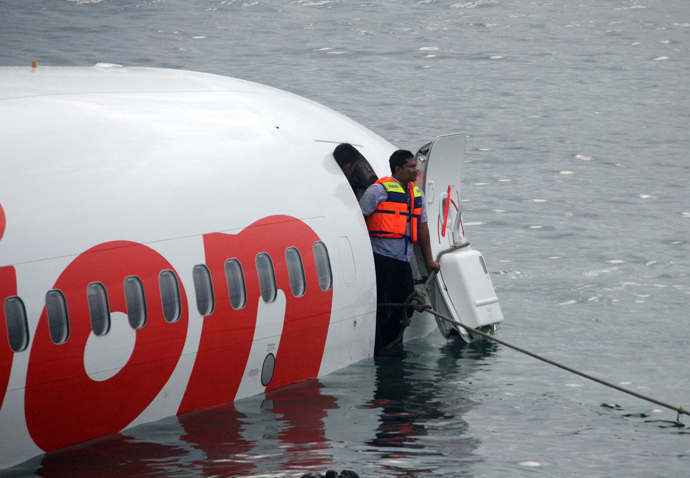 This handout photo released by the Indonesian Police on April 13, 2013 shows a man standing at the door of a Lion Air Boeing 737 after the aircraft skidded off the runaway during landing at Bali's international airport near Denpasar (AFP Photo / Indonesian Police)