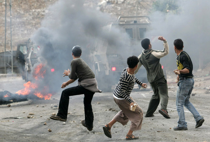 Palestinian boys throw rocks at an Israel army vehicule during an army operation in the refugee camp Al-Faraah, outside the West Bank City of Jenin (AFP Photo)
