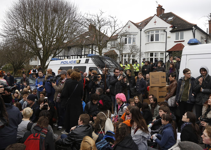 Demonstrators sit in the road during a UK Uncut protest outside the home of welfare minister David Freud, in north London April 13, 2013. (Reuters/Luke MacGregor)