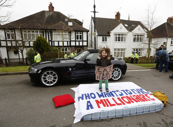 Eight Year old Lucian Shalmy-Freeman jumps on a mattress during a UK Uncut protest outside the home of welfare minister David Freud, in north London April 13, 2013. (Reuters/Luke MacGregor)