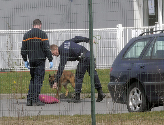 Policemen patrol with a dog to find evidences, on April 13, 2013 in a yard of Sequedin prison, after an inmate, Redoine Faid, managed to escape using explosives after holding five wardens hostages. (AFP Photo/Francois Lo Presti)