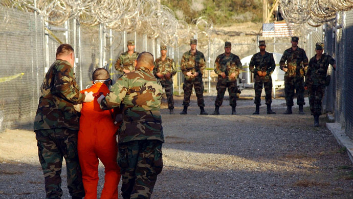 Police escort a detainee to his cell at Naval Base Guantanamo Bay, Cuba, this file photograph taken on January 11, 2002.  (Reuters/Shane T. McCoy/Department of Defense)