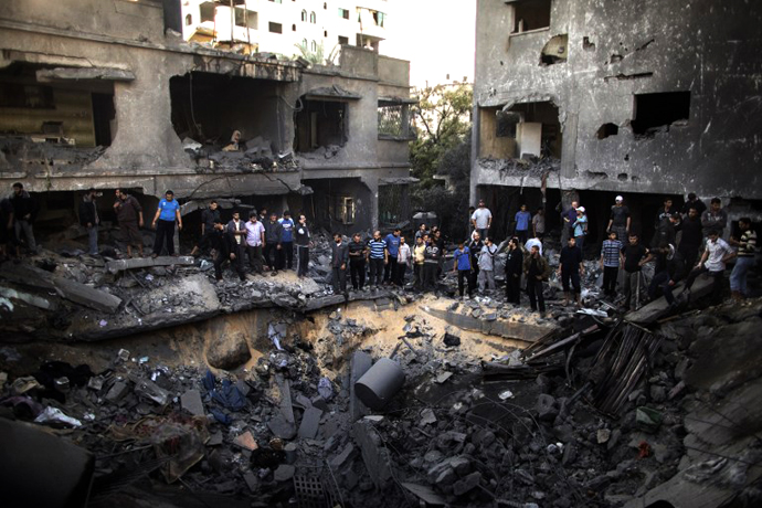 Palestinian men gather around a crater caused by an Israeli air strike on the al-Dallu family's home in Gaza City on November 18, 2012. (AFP Photo / Marco Longari)
