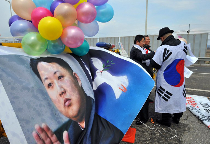 South Korean activists set balloons on a banner showing pictures of North Korean leader Kim Jong-Un. (AFP Photo / Jung Yeon-Je)