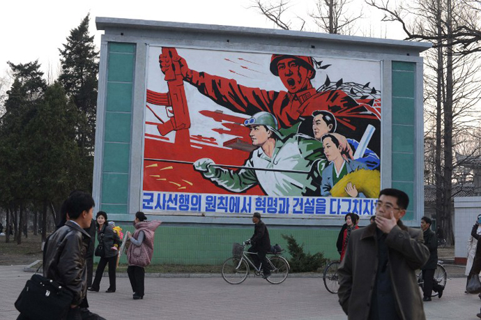 North Koreans stand in front of a political mural in Pyongyang. (AFP Photo / Pedro Ugarte)
