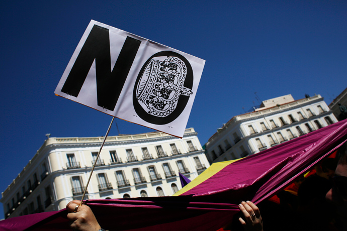 People hold a Spanish Republican flag and a placard as they take part in a rally to mark the 82nd anniversary of Spain's Second Republic in Madrid April 14, 2013 (Reuters / Susana Vera)