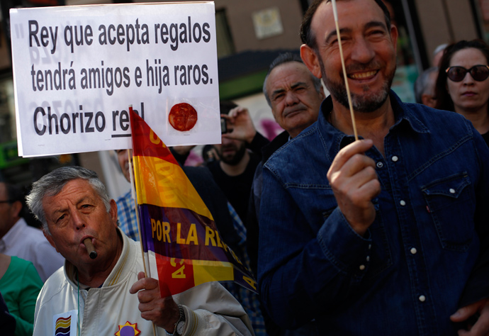 "A man holds a placard that has a slice of chorizo sausage during a rally to mark the 82nd anniversary of Spain's Second Republic in Madrid April 14, 2013. The placard reads, "" King who accepts gifts will have strange friends and daughters. Royal chorizo!!!"" Chorizo is slang for thief in Spanish (Reuters / Susana Vera)"