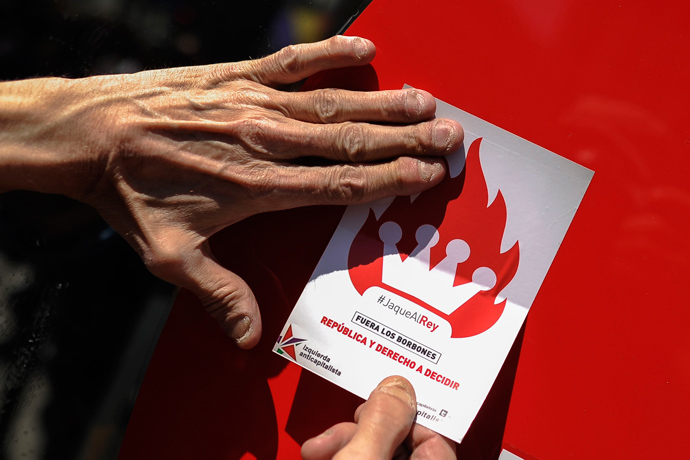 "A man stick a sticker reading ""Bourbon monarchy out, Republic and the right to decide"" during a demonstration by Republicans in Madrid, on April 14, 2013 to commemorate the 82nd anniversary of the Second Republic (AFP Photo / Pedro Armestre)"