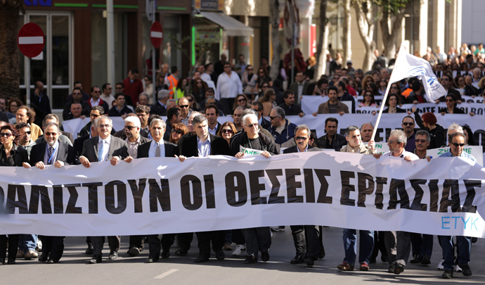 Employees of the bank hold banners as they march towards the parliament on April 4, 2013 during a demonstration in the Cypriot capital, Nicosia, over fears that pensions may be at risk under Cyprus's bailout, as more details emerged of biting austerity measures imposed on the cash-strapped island (AFP Photo / Patrick Baz)