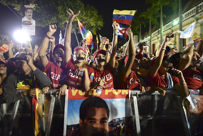 Supporters of Venezuelan acting President Nicolas Maduro celebrate after knowing the election results in Caracas on April 14, 2013. (AFP Photo / Juan Barreto)