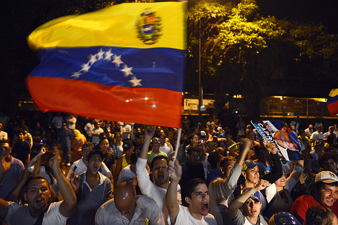 Supporters of the Venezuelan Opposition leader Henrique Capriles wave national flag outside the place were he deliver a press conference in Caracas on April 15, 2013. (AFP Photo / Leo Ramirez)