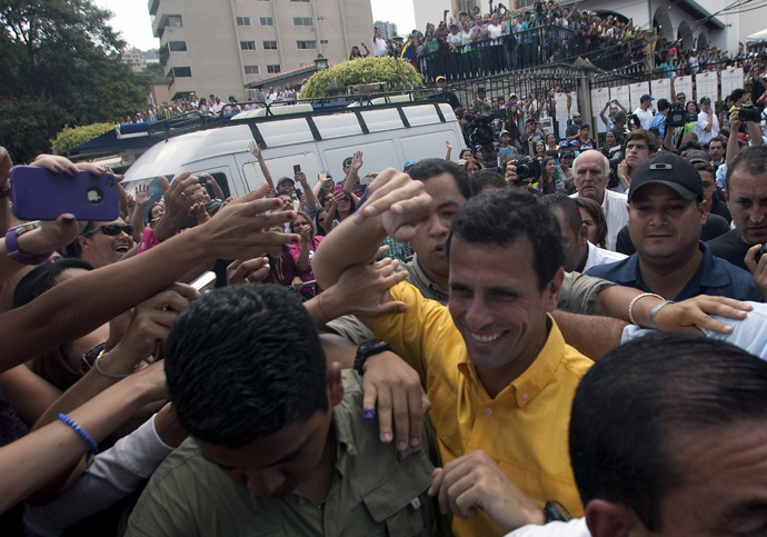 Venezuelan opposition presidential candidate Henrique Capriles greets supporters after voting in Caracas, on April 14, 2013 (AFP Photo / Geraldo Caso)