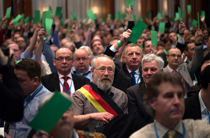 "Members of Germany's anti-euro party AfD ""Alternative fuer Deutschland"" (Alternative for Germany) hold up green cards during the first party meeting on April 14, 2013 in Berlin. (AFP PHOTO / Johannes Eisele)"
