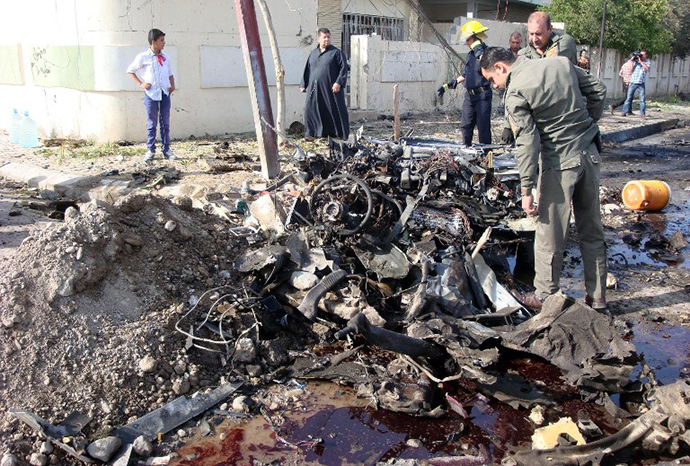 A man looks at the remains of a car bomb in the northern Iraqi city of Kirkuk on April 15, 2013. (AFP Photo / Marwan Ibrahim)