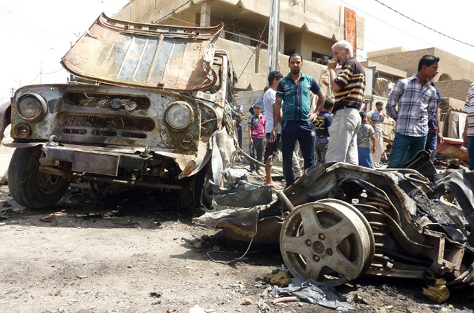 Iraqis look at the remains of vehicles damaged following an explosion in the al-Obaidi neighborhood, east of Baghdad on April 15, 2013. (AFP Photo / Ali Al-Saadi)