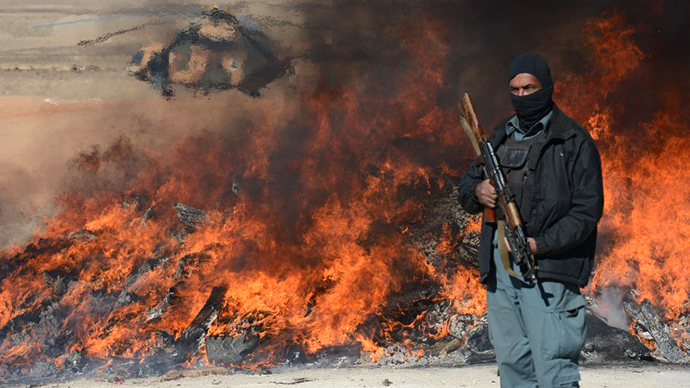 This photo taken on December 19, 2012 shows an Afghan policeman standing guard as a pile of narcotics is burned by officials on the outskirts of Jalalabad Nangarhar province. (AFP Photo / Shan Marai)