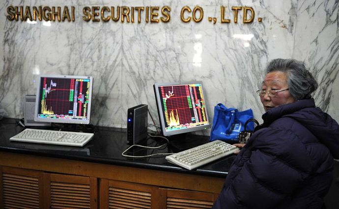 An elderly investor looks at stock prices at a securities exchange in Shanghai on February 22, 2013. (AFP Photo / Peter Parks)