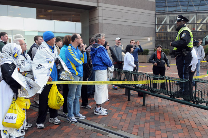 Runners listen to directions from a Boston Police officer at the corner of Stuart Street and Dartmouth Street after two explosive devices detonated at the finish line of the 117th Boston Marathon on April 15, 2013 in Boston, Massachusetts (AFP Photo)