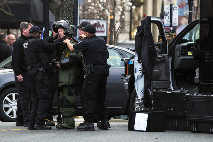 A law enforcement bomb technician is helped to put on his protective suit, before he set off a controlled detonation of a suspicious object during a search for a suspect in the Boston Marathon bombing, in Watertown, Massachusetts April 19, 2013. (Reuters / Lucas Jackson)