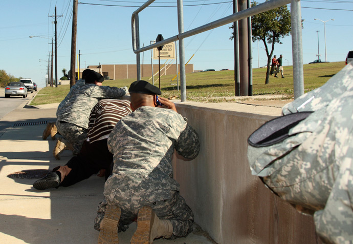 Bystanders crouch for cover as shots rang out from Fort Hood's Soldier Readiness Processing Center, while law enforcement officers run toward the sound of the gun, November 5, 2009 (Reuters / Jeramie Sivley)