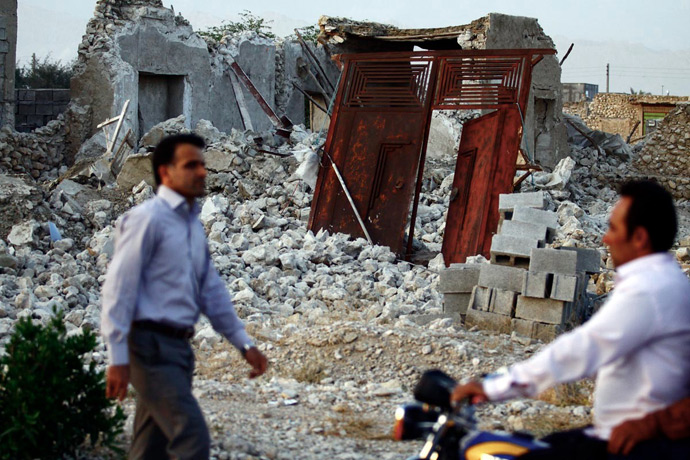 Iranians walk past the ruins of a destroyed house in the town of Shonbeh, southeast of Bushehr, on April 9, 2013 after a powerful earthquake struck near the Gulf port city of Bushehr (AFP Photo / STR)