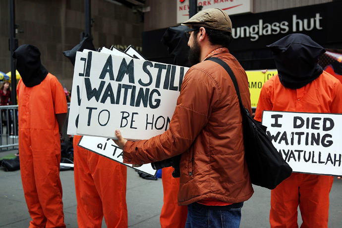 "Activists in Times Square, dressed in orange prison jumpsuits, participate in a nationwide ""Day of Action to Close Guantanamo & End Indefinite Detention"" on April 11, 2013 in New York City (Reuters / Spencer Platt)"