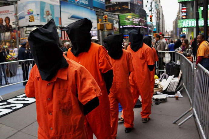 "Activists in Times Square, dressed in orange prison jumpsuits, participate in a nationwide ""Day of Action to Close Guantanamo & End Indefinite Detention"" on April 11, 2013 in New York City (AFP Photo / Spencer Platt)"