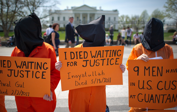 Black hooded human rights activists hold banners demanding the closing of Guantanamo during a protest, part of the Nationwide for Guantanamo Day of Action, outside the White House in Washington DC on April 11, 2013 (AFP Photo / Mladen Antonov)