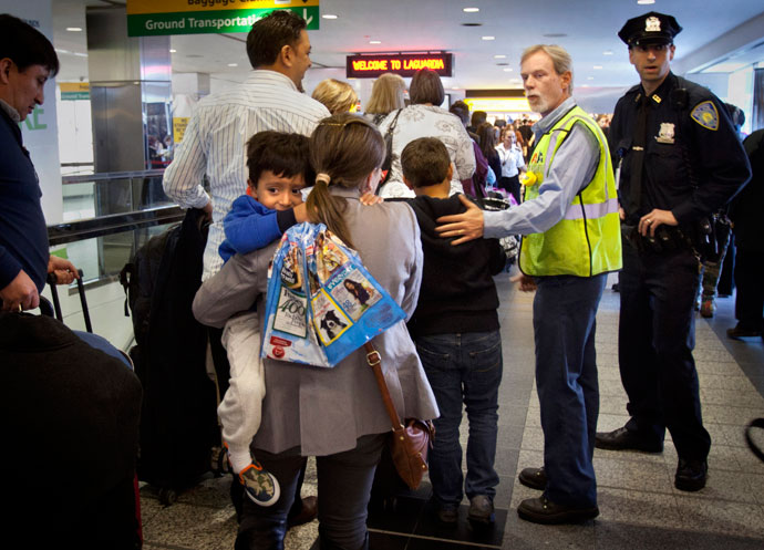 American Airlines employee Paul Reinold helps to expedite people though the security line at LaGuardia airport after it was shut down for a time due to a security scare in New York, April 16, 2013.(Reuters / Carlo Allegri)