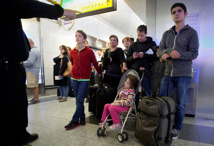 A family listens to a police officer give them instructions in the security line at LaGuardia airport after it was shut down for a time due to a security scare in New York, April 16, 2013.(Reuters / Carlo Allegri)