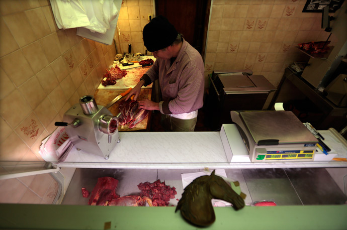 A butcher, prepares horsemeat as he works in his horse butchery shop in the old city of Nice (Reuters / Eric Gaillard)