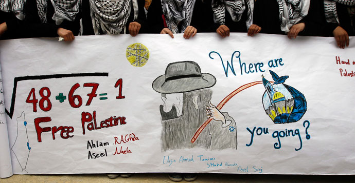 Palestinian school girls hold a banner during a rally marking Prisoner Day in the West Bank city of Hebron April 17, 2013.(Reuters / Ammar Awad)