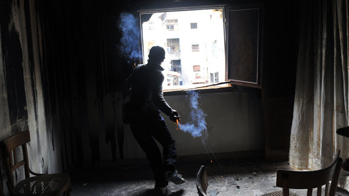 A rebel fighter throws a homemade grenade towards Syrian government forces through a window at a flat in the Salaheddine neighbourhood of Aleppo on February 16, 2013.(AFP Photo / Bulent Kilic)