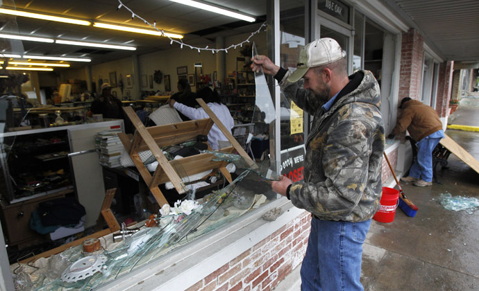 Brandon Smith removes broken glass from the West Thrift Shop after an explosion at a fertilizer plant damaged the store in the town of West, near Waco, Texas April 18, 2013 (Reuters)