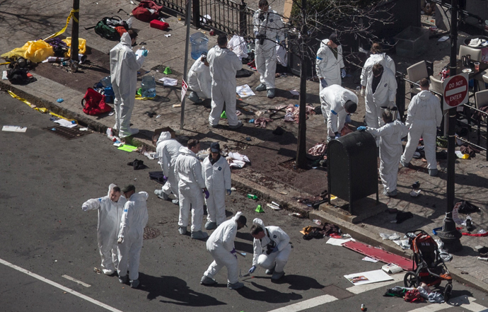 Investigators survey the site of a bomb blast on Boylston Street a day after two explosions hit the Boston Marathon in Boston, Massachusetts April 16, 2013 (Reuters / Adrees Latif)