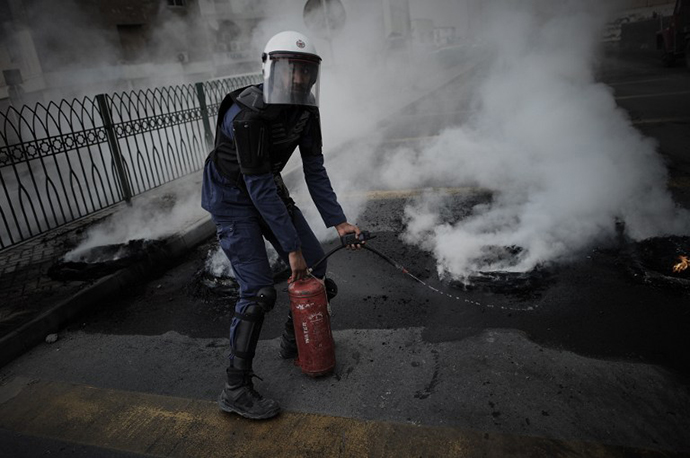 A Bahraini Policeman extinguishes tyres burning during clashes with riot police following a protest against the arrival of Bahrain Formula One Grand Prix on April 18, 2013 in the village of Diraz, west of Manama. (AFP Photo / Mohammed Al-Shaikh)