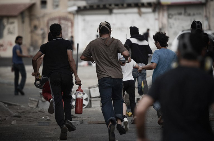 A Bahraini protester runs away carrying a pressurized fire extinguisher that is used to shot iron arrows towards riot police during clashes following a protest against the arrival of Bahrain Formula One Grand Prix on April 18, 2013 in the village of Diraz, west of Manama. (AFP Photo / Mohammed Al-Shaikh)