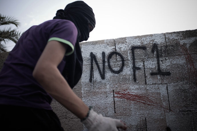 A Bahraini masked protestor writes graffiti against the upcoming Bahrain Formula One Grand Prix on the sidelines of an anti-regime rally in support of political activists held in jail in the village of Jid Ali, north-east of Isa Town, on April 17, 2013 (AFP Photo / Mohammed Al-Shaikh)