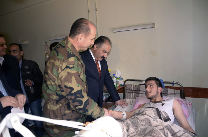 Syrian government officials and military personnel visit a victim of chemical weapons at a hospital in Aleppo, March 21, 2013. (Reuters/George Ourfalian)