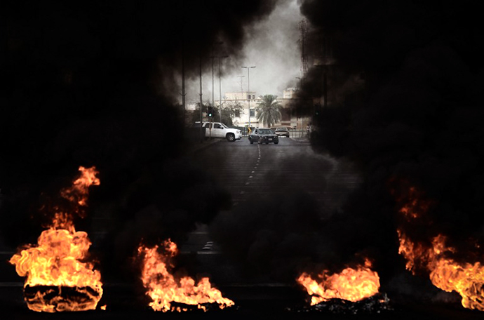 Tyres placed on the road by anti-regime protestors are burning during clashes with riot police following a protest against the arrival of Bahrain Formula One Grand Prix on April 18, 2013 in the village of Diraz, west of Manama. (AFP Photo / Mohammed Al-Shaikh)