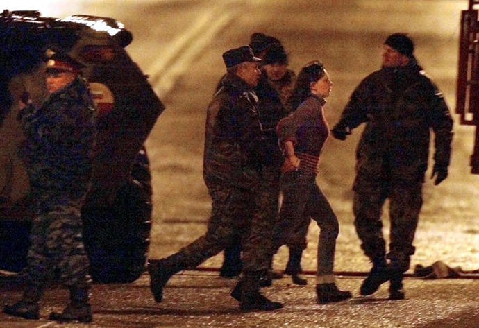 Russian special forces officers evacuate early 26 October 2002an unidentified hostage from the theater in Moscow, where a number of Chechen rebels were holding some 700 theatre-goers hostage since 23 October. (AFP Photo / Alexander Nemenov)